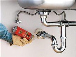 man using great stuff under sink with plumbing