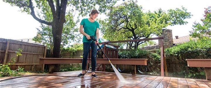 woman spraying off deck with power washer