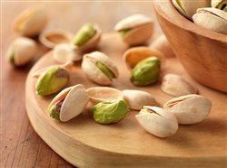 close up of a pistachios and a wooded bowl