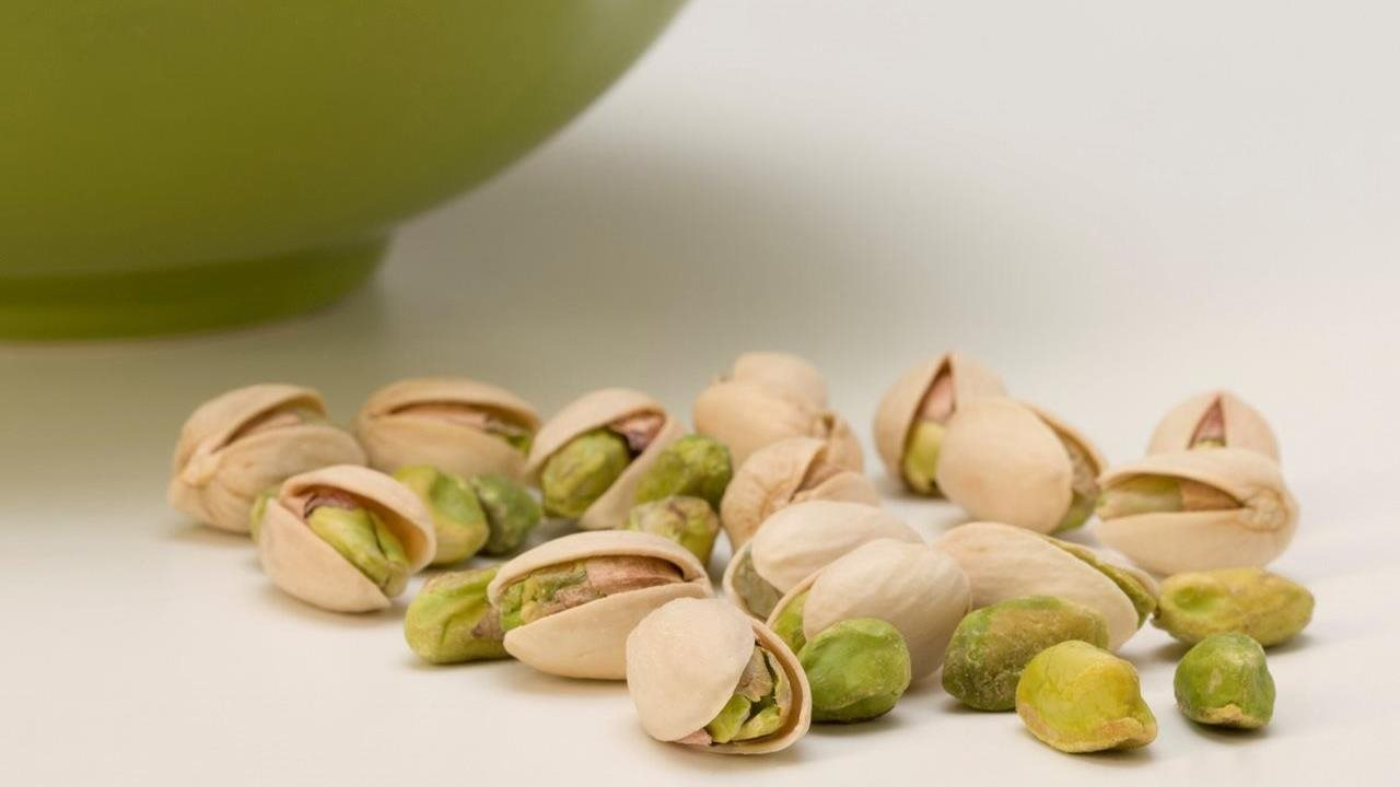 Pistachios in and out of the shell next to a green bowl