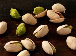 Shelled pistachios on a dark wood surface.