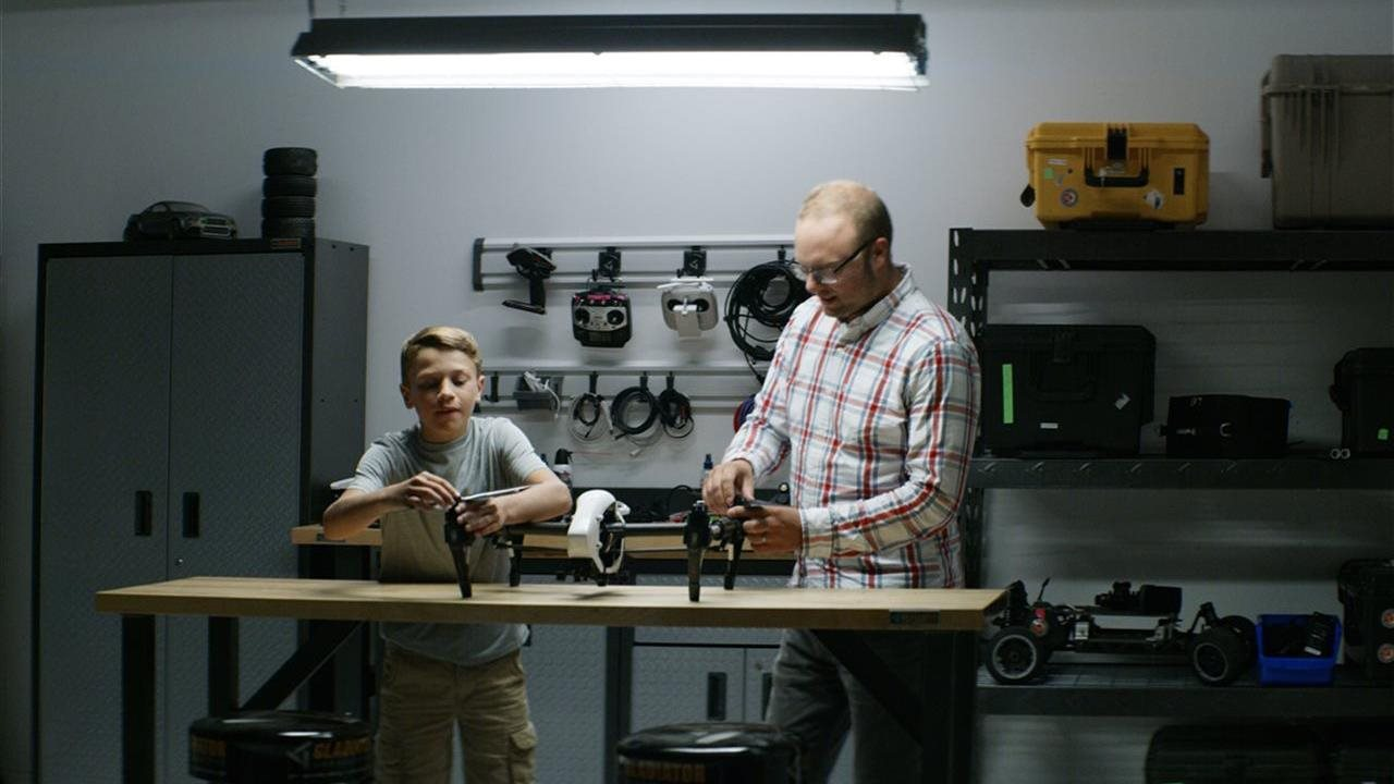 boy and dad working in a clean garage workshop