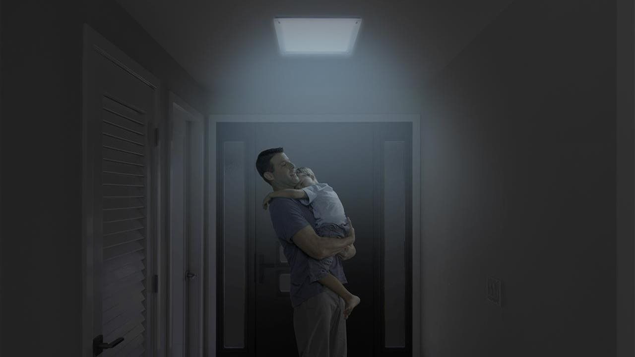 Father holding son in hallway at night below solar powered night light in ceiling