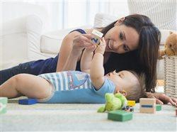 Young mother plays with baby on living room floor.