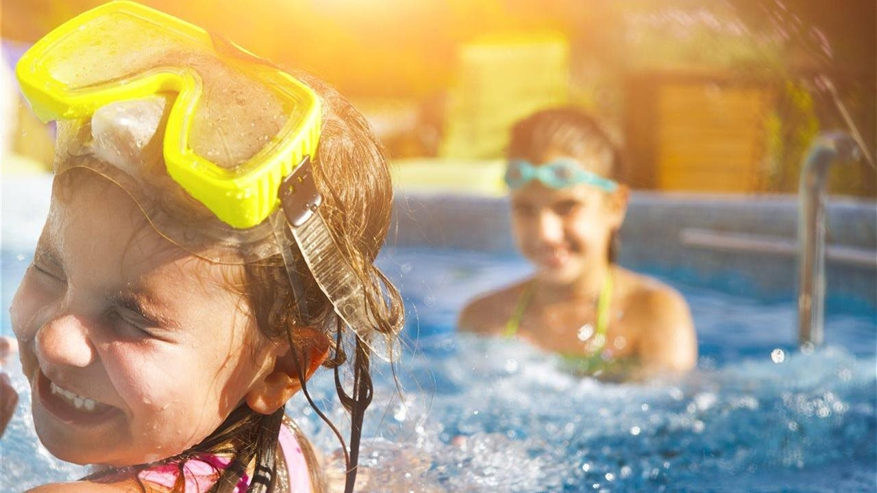 Little girl with goggles in pool with Mom