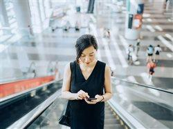 Business woman going up an escalator while browsing on her smartphone.