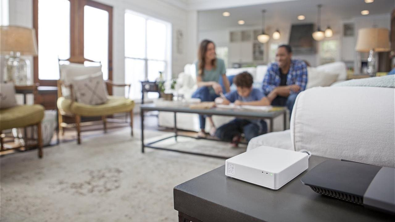 security system close up with family in their living room in the background