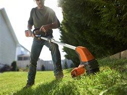 man using weed whipper on edge of lawn