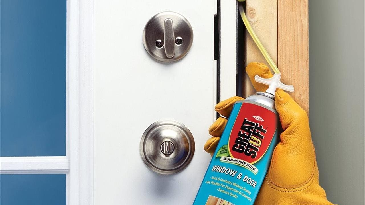 person using great stuff to seal around a door frame.
