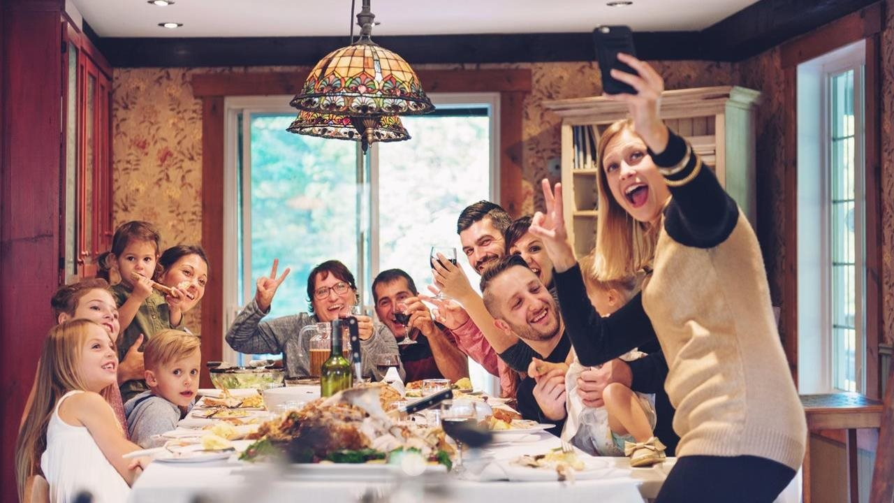 family gathering for dinner and woman taking a selfie