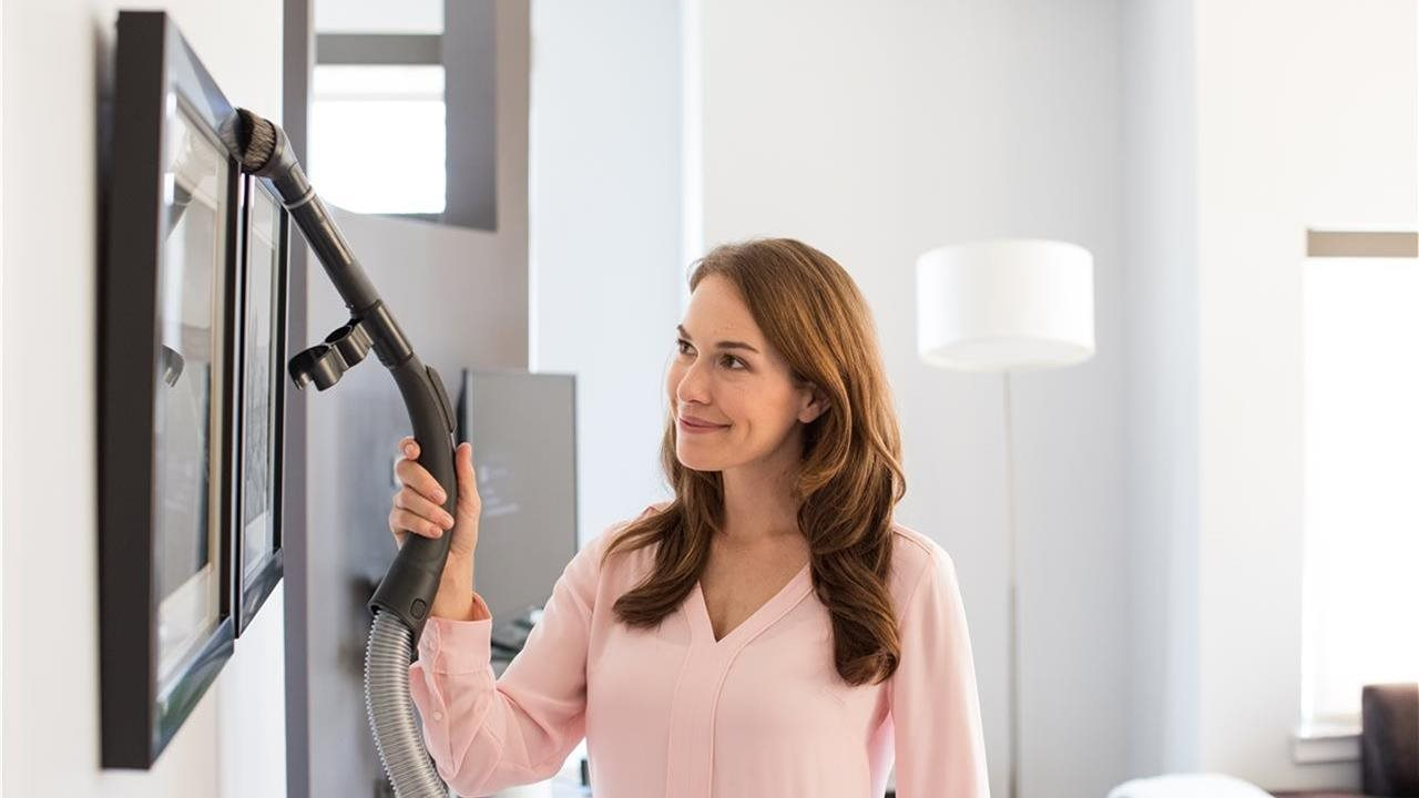 woman using a vacuum to clean the top of picture frame