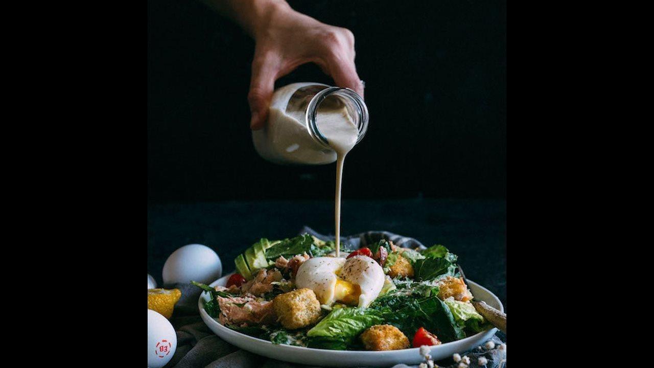 BLT Salmon Caesar Salad with dressing pour
