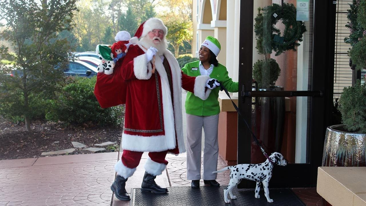santa with bag of toys on his back walking puppy into hotel