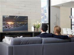 couple watching big screen tv in living area