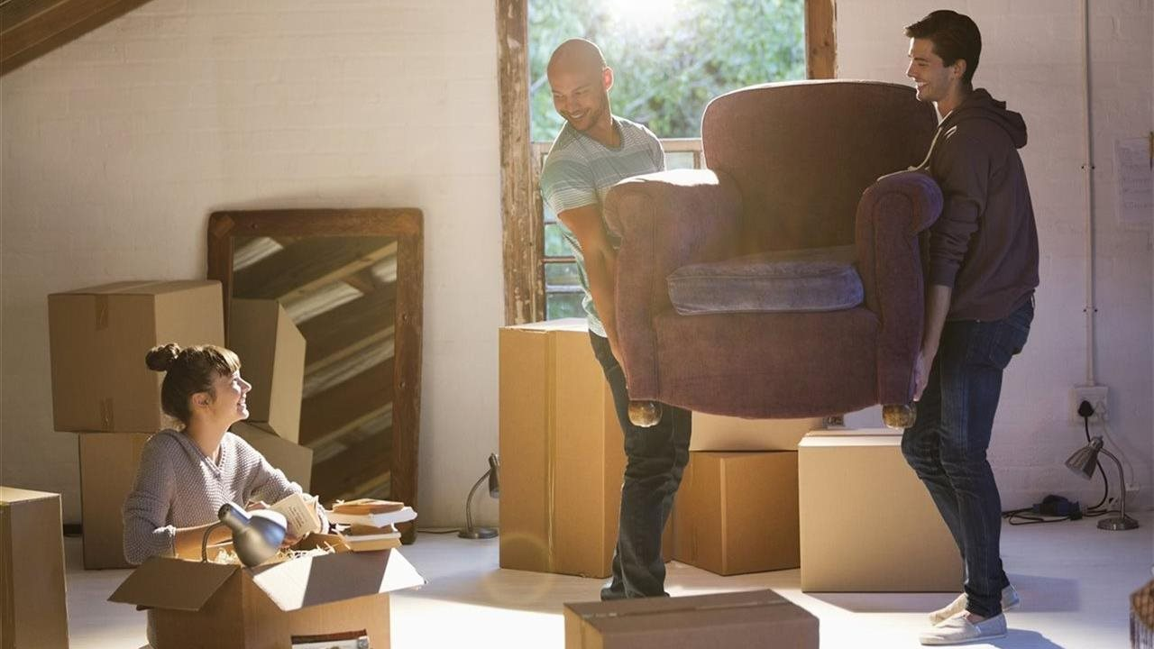 woman packing a moving box and two men moving a chair