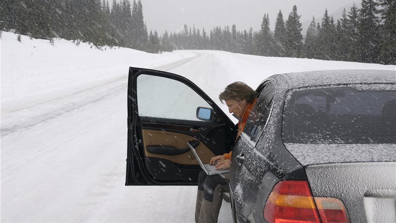 man in a car using a laptop on the side of the road in the winter
