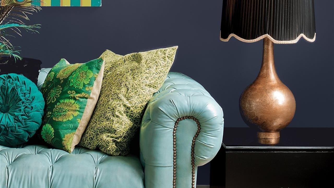 Trendy living room with dark blue wall and aqua couch, and a variety of textures in accessories.