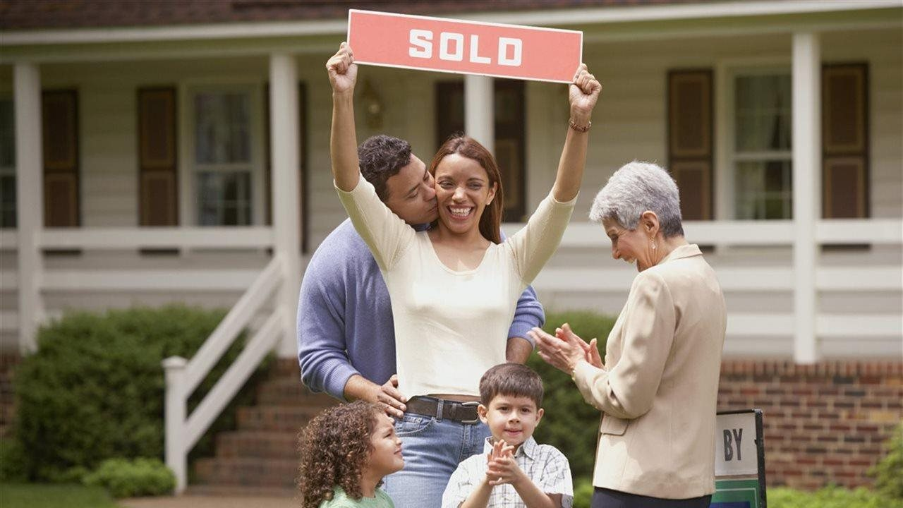 Happy family holding SOLD sign in front of brand new home