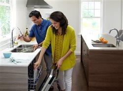 couple loading dishwasher in upscale kitchen