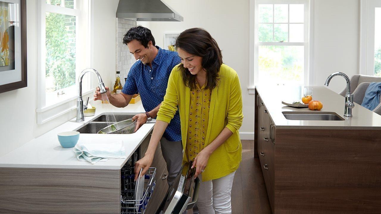 couple loading dishwasher in upscale kitchen