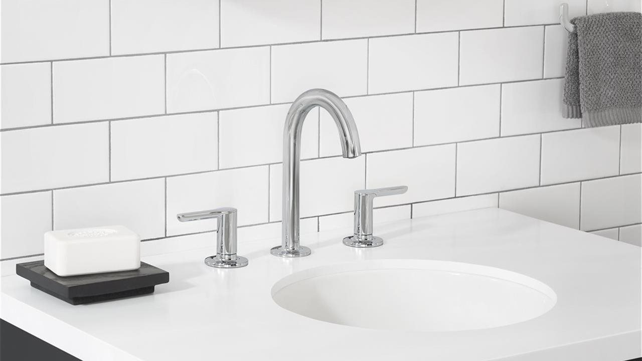 close up of widespread lever handled faucets on an upscale sink