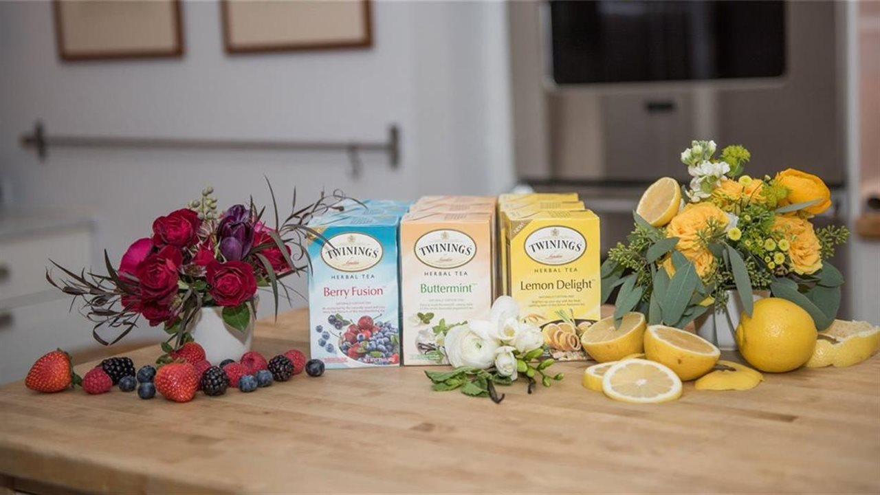 assortment of teas arranged with flowers on a counter in a kitchen