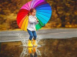 little girl in rain boots jumping in puddle holding rainbow umbrella