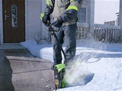 homeowner dealing with a snow storm using a greenworks blower