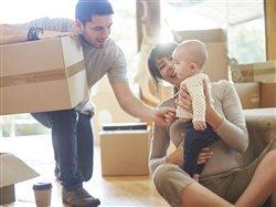Young mother father and baby in house on moving day