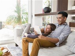 Couple on sitting room sofa looking at digital tablet