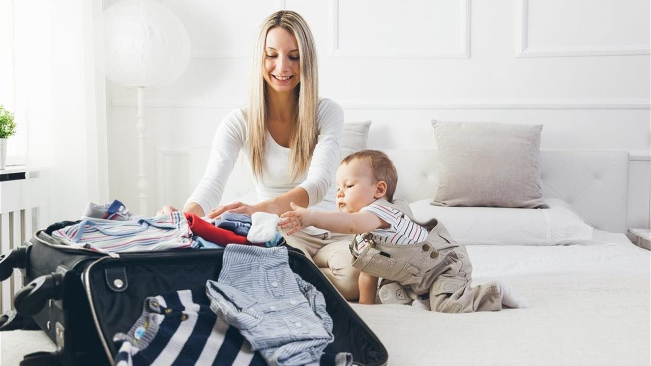Happy young mother packing suitcase on bed with baby