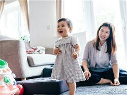 happy toddler walking as mother looks on