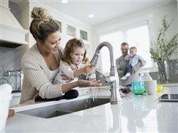 mother hleping daughter wash her hands in the kitchen sink while dad and younger brother look on