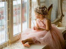 little girl sitting on window seat looking out the window