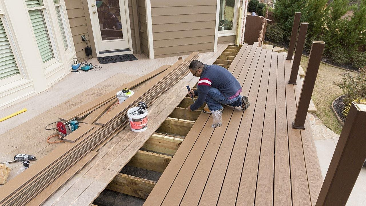 Man building deck on house using power tools