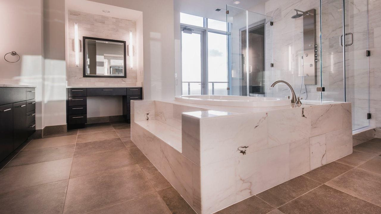 stunning bathroom with large tile floor and bath surround