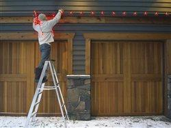 man raking down Christmas lights over garage door