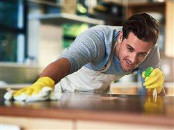 young man wiping down a counter top in the kitchen