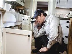 man with flashlight looking under the sink in a kitchen