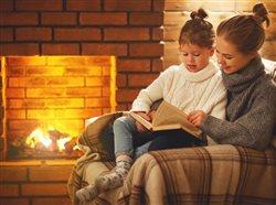 mom and daughter reading book by the fire place