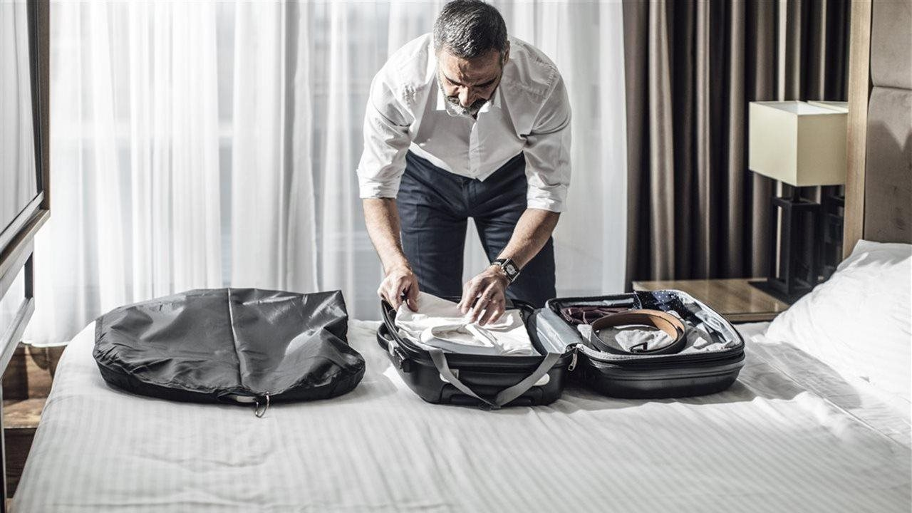 Man unpacking suitcase on bed in a hotel room