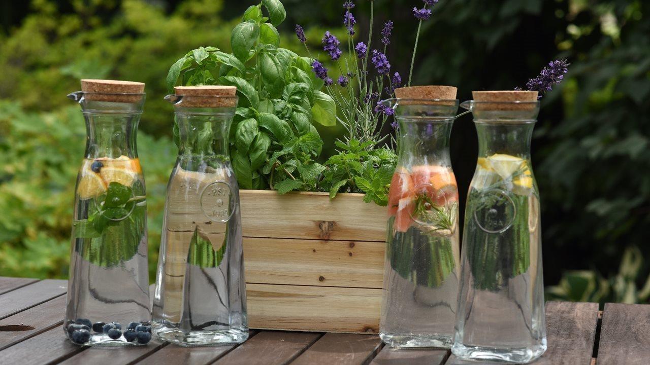 Herb water carafes next a plant arrangement