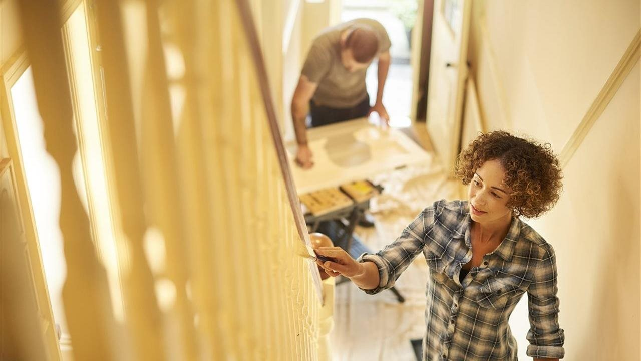 couple painting a staircase in their home