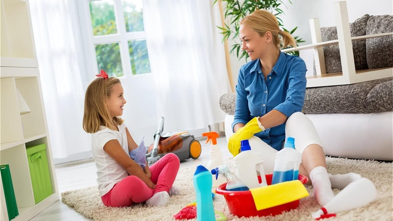 Mom and her daughter in livingroom with cleaning products