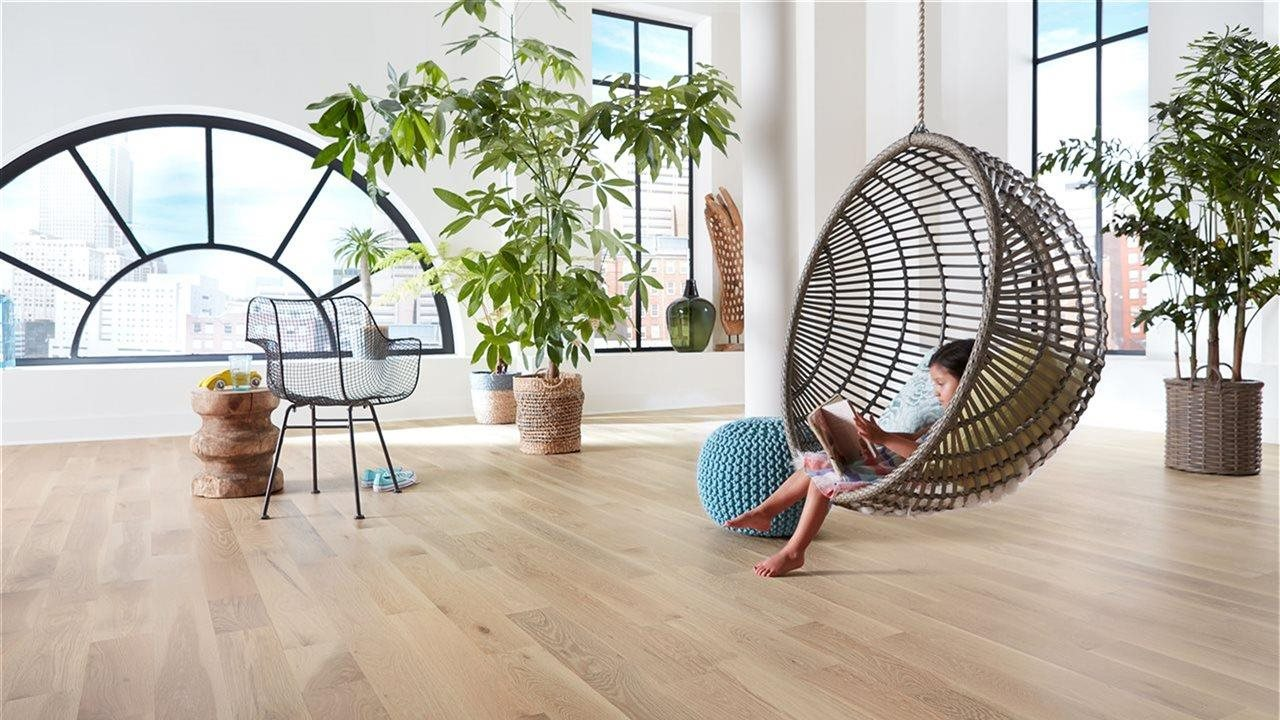kid reading in hanging chair over beautiful wood floor