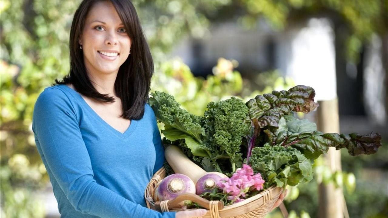 woman holding basket of garden vegetables