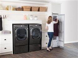 woman using home clothes styler in laundry room