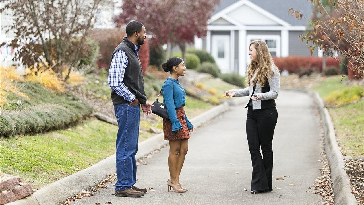 young couple walking and talking with realtor