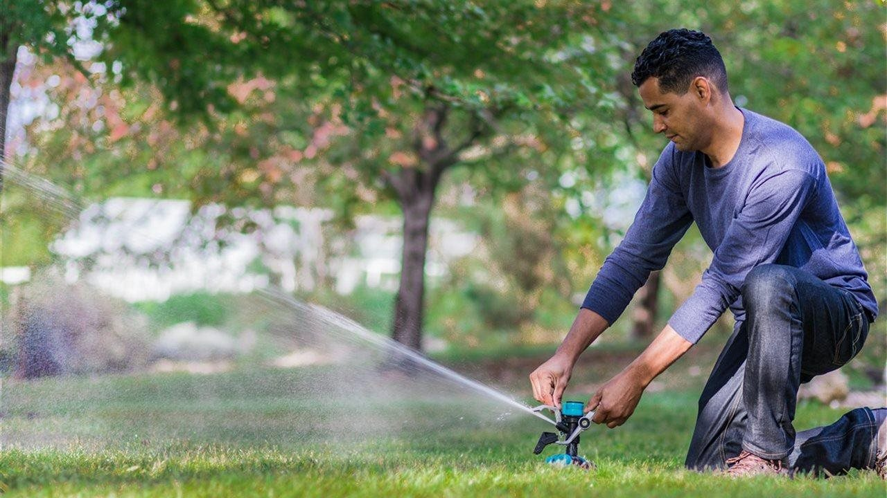man setting a sprinkler in his lawn