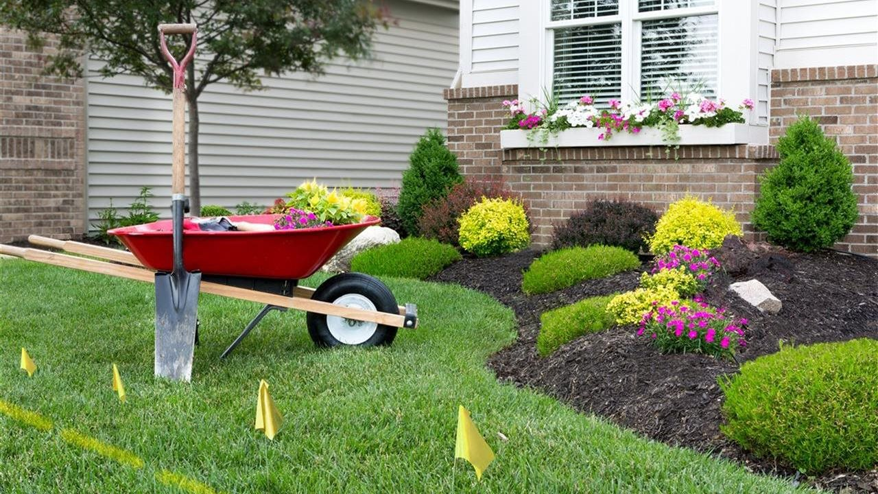 Beautiful landscaped lawn garden with wheelbarrow and shovel